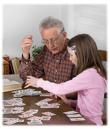 Young girl playing cards with her Grandfather
